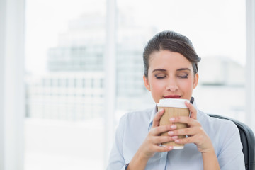 Peaceful classy brown haired businesswoman enjoying coffee smell