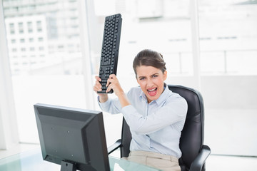 Annoyed classy brown haired businesswoman throwing her keyboard