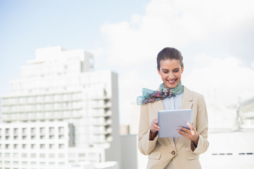 Content smart brown haired businesswoman using a tablet pc