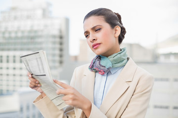 Concentrated smart brown haired businesswoman reading a newspape