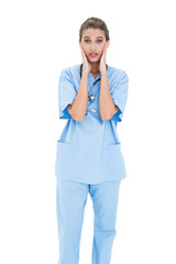 Astonished brown haired nurse in blue scrubs posing with head in
