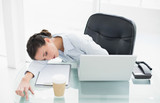Exhausted stylish brunette businesswoman sleeping on her desk