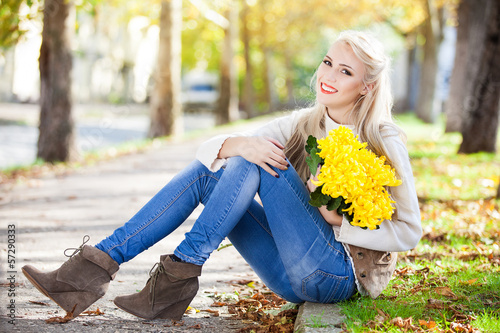woman with bouquet of flowers in hand in autumn park