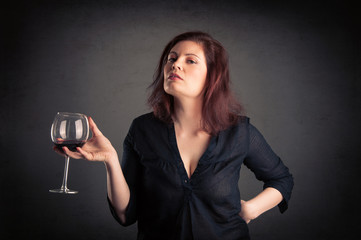 Woman with glass of red wine in her hand on grunge background.