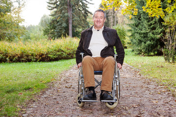 Man in wheelchair in autumnal park