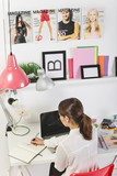 Fashion woman blogger working in a creative workspace. poster