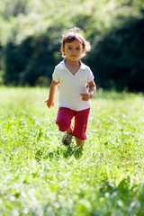 active 2 year old child running in a green park