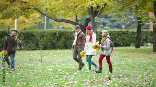 Two kids and their parents walking in the park