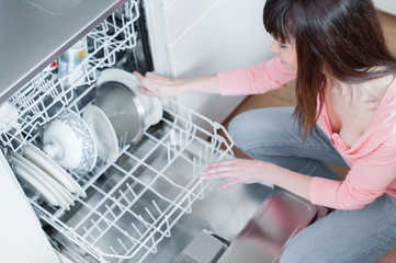 A beautiful woman using a dishwasher in a modern kitchen. domest