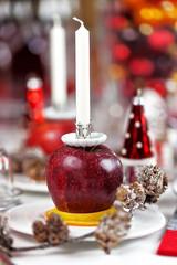 Weihnachtliche Tischdekoration mit Apfel und Kerze