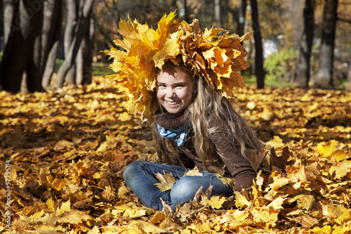 Girl sitting in autumn leaves
