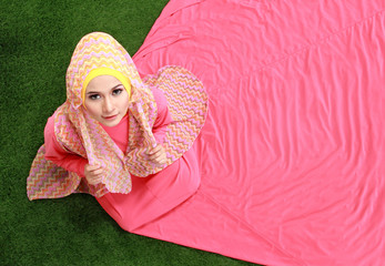 Young muslim girl sitting on grass
