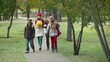 Two kids and their parents walking together in the park