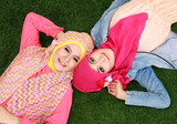 two muslim woman lying on grass
