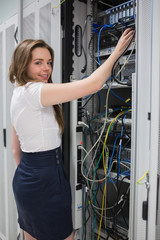 Smiling brunette fixing wires of server