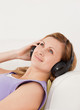 Cute blond-haired woman listening to music lying on the sofa