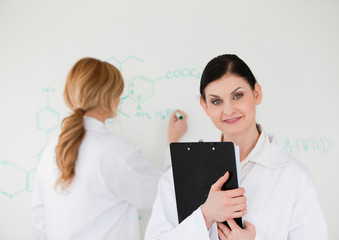 Scientist posing while another is writing a formula on a whitebo