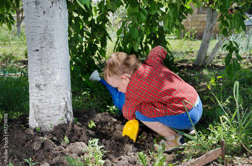 Happy little boy digging with his spade