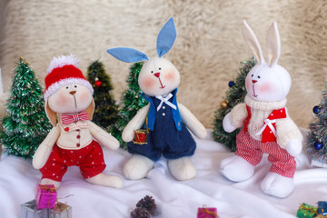 Christmas toy rabbits on the background trees