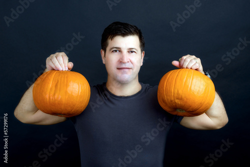 man shows halloween pumpkins isolated on black background
