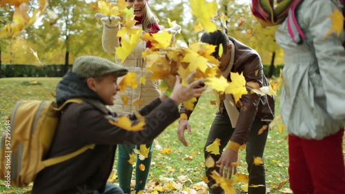 Happy family of four playing with leaves in the park in autumn