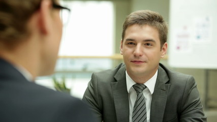 Businessman speaking to his colleague in the office