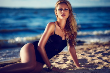 glamor sexy blond model with perfect skin in black swimsuit