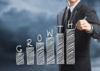 Business man writing growth chart concept