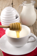 honey flows into a cup with warm milk