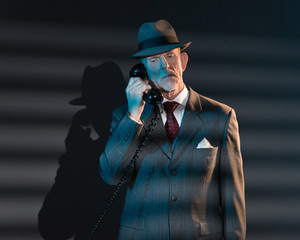 Retro detective man calling with vintage telephone at night in o