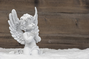little white angel ion wooden background
