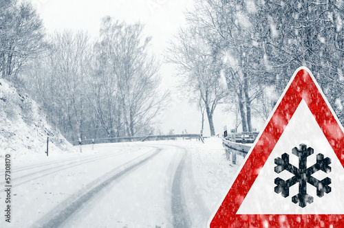 canvas print picture Snowy curvy road with traffic sign