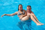 Father and daughter in tropical swimming pool