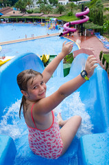Happy young girl on tropical water slide