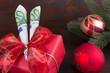 Dekoratives Geldschenk zu Weihnacht mit roten Kugeln