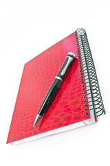 Pen on red spiral notebook isolated on white