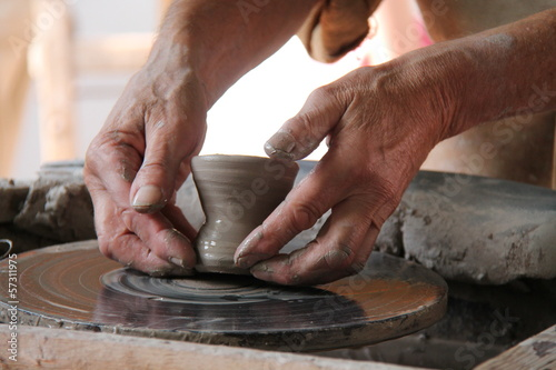 A Clay Pot Being Carefully Lifted from the Potters Wheel.