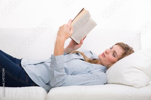 frau liest buch auf der couch