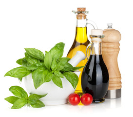 Olive oil and vinegar bottles with basil and tomatoes