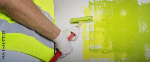 Painter painting the office wall with roller paint