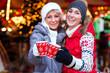Freunde trinken Glühwein auf Weihnachtsmarkt zur Adventszeit