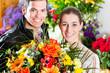 Floristin und Kunde in Blumenladen