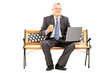 Mature businessman with coffee cup working on a laptop