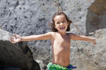 Niña feliz delante de unas rocas