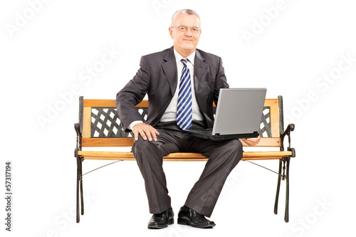 Mature professional man sitting on a bench working on laptop