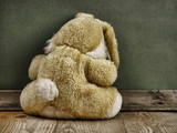 old abandoned toy bunny on a wooden floor