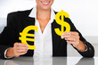 Businesswoman Holding Euro And Dollar Sign At Desk
