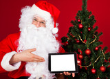 Portrait of a happy santa holding digital tablet