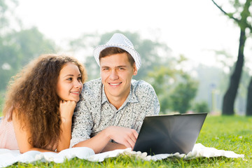 couple lying together in a park with laptop