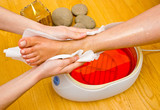 woman foot in paraffin bath at the spa poster